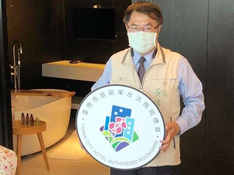 臺南市長黃偉哲親自展示「臺南市旅館業合法房間標章」